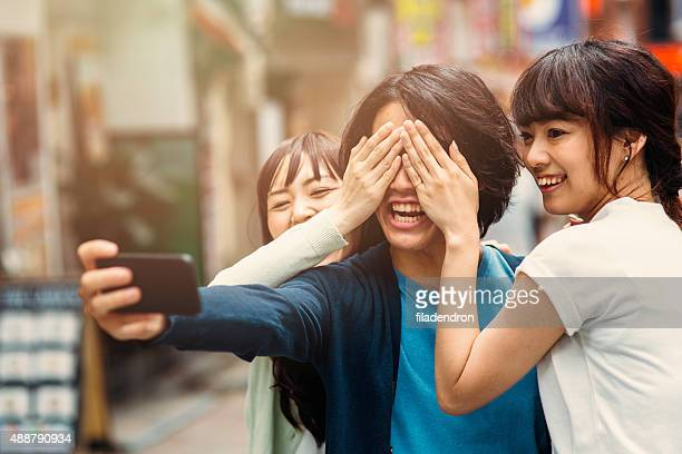 Happy japanese friends taking a selfie
