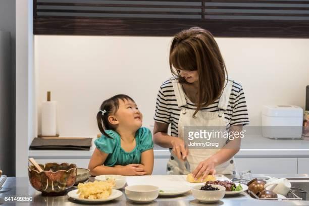 幸せな日本の少女と自宅の食糧を準備する母親