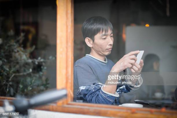 happy japanese man relaxing holidays at the cafe - ミッドアダルト stock pictures, royalty-free photos & images