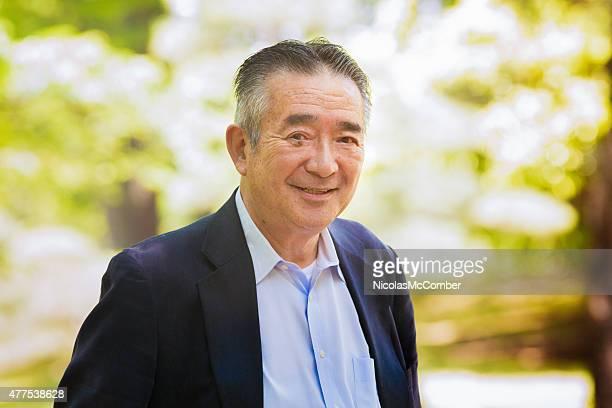 Happy japanische Alter Mann im park lächelnd an einem sonnigen Tag