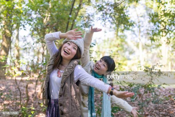 緑の森で遊んで幸せな日本の姉妹