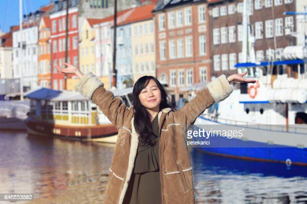 Happy japanese woman on holiday standing with arms spread open in Nyhavn, Copenhagen