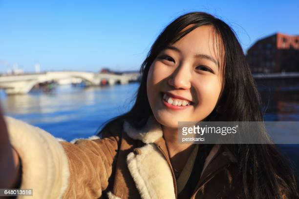 Lycklig japansk kvinna turist tar selfie i Nyhavn, Copenhagen