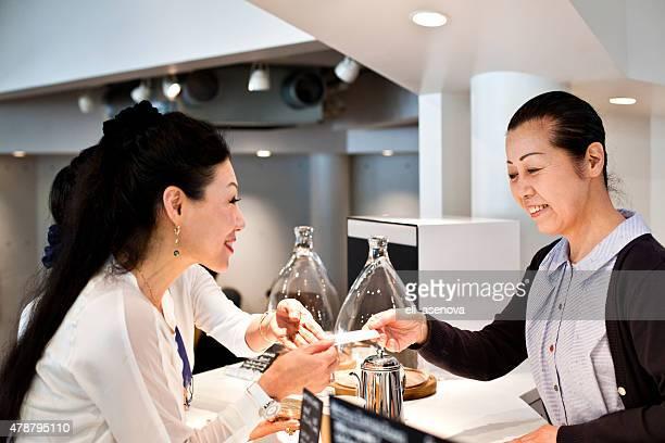 幸せな女性のお支払いには、クレジットカード、カフェ東京