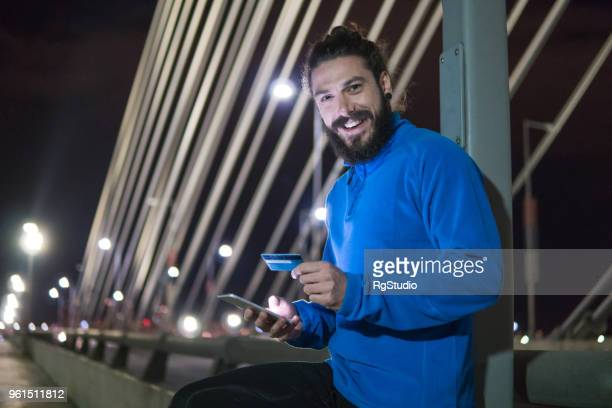 happy jogger with credit card and mobile phone - charging sports stock pictures, royalty-free photos & images