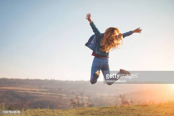 happy jump by girl in nature - joy stock pictures, royalty-free photos & images