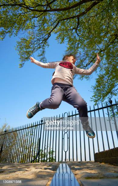 happy jump by girl over the james bradley's meridian line at the royal observatory in greenwich, england. - jumping stock pictures, royalty-free photos & images