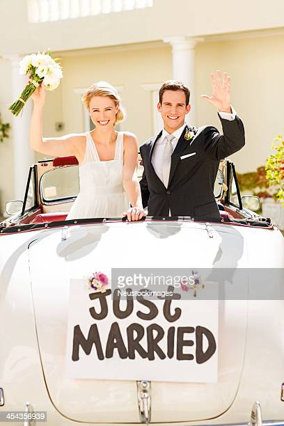 Happy Just Married Couple Waving In Car
