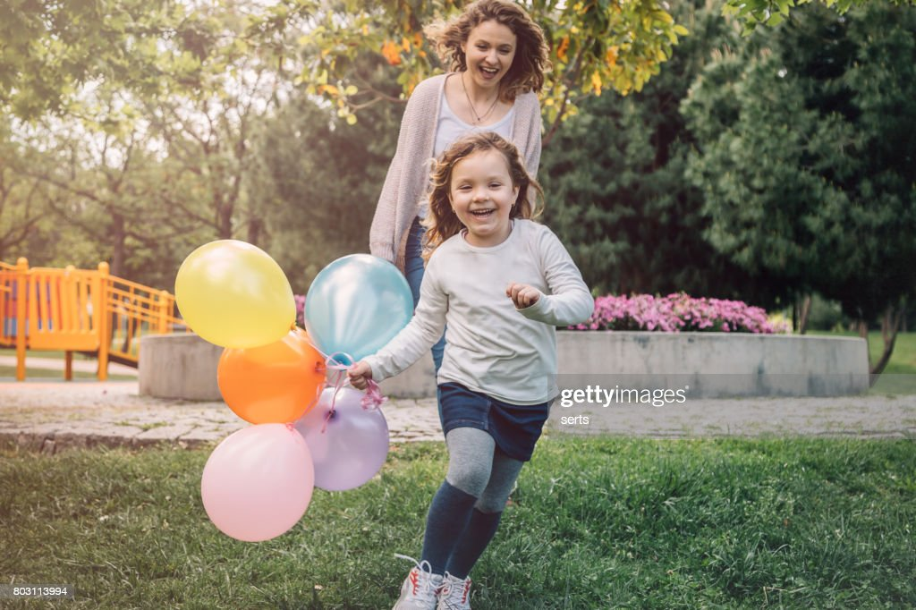 Happy kid girl and her mother having fun outdoors at sunny day : Stock Photo