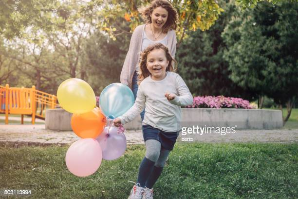 Happy kid girl and her mother having fun outdoors at sunny day