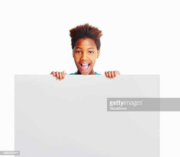 Happy kid sosteniendo Cartelera contra blanco copyspace