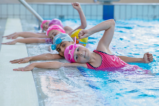 happy kids at the swimming pool. young and successful swimmers pose. 1007485564