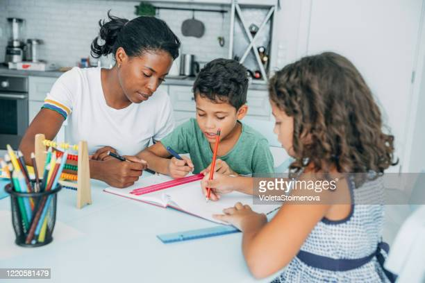 happy kids doing their homework with mom. - homeschool stock pictures, royalty-free photos & images