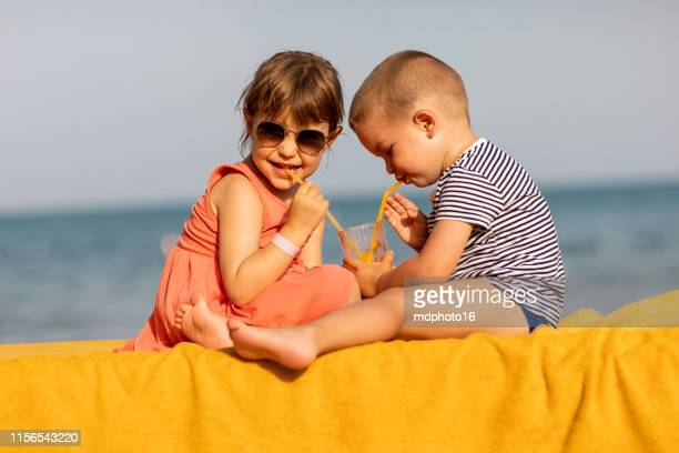 happy kids drinking juice together on the beach - famiglia con due figli foto e immagini stock