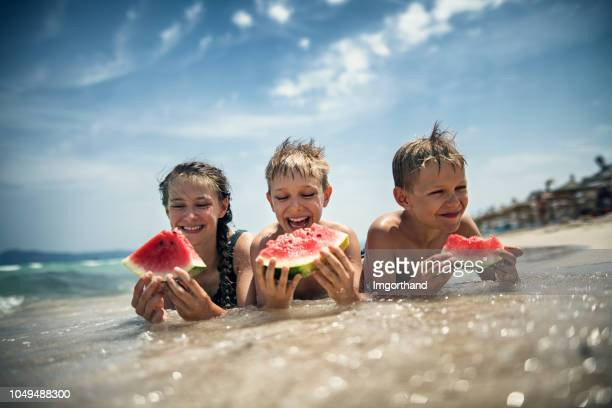 happy kids eating watermelon on the beach - watermelon stock pictures, royalty-free photos & images