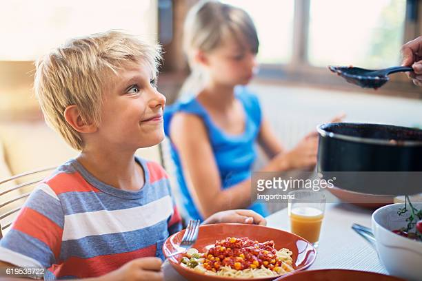 Happy kids enjoying delicious pasta meal