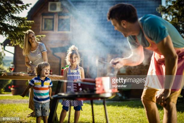 happy kids enjoying in picnic day with their parents in the backyard. - bbq stock pictures, royalty-free photos & images
