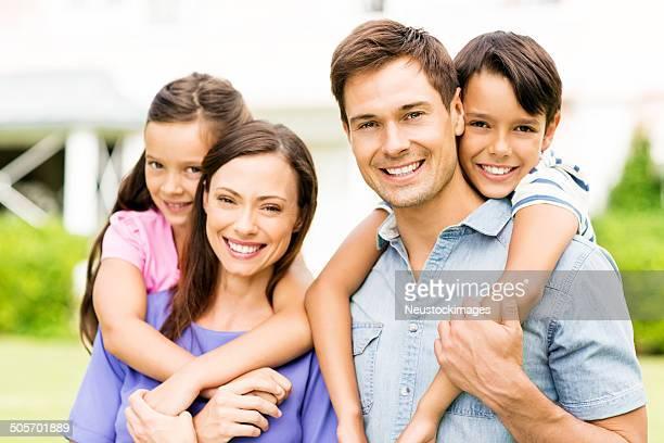 Glückliche Kinder Reiten auf die Eltern Genießen Huckepack nehmen