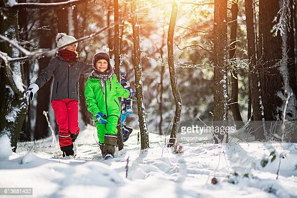 Happy kids enjoying sunny winter day in forest