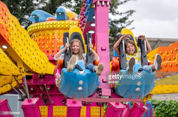 happy kids having fun in an amusement park - amusement park ride stock pictures, royalty-free photos & images