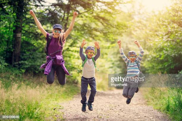 Happy kids hikers jumping with joy in forest