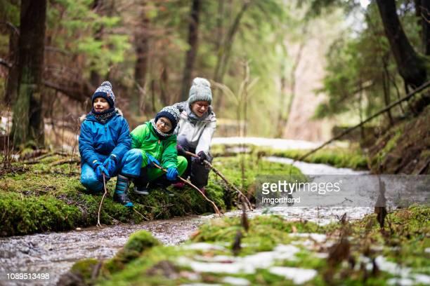escursionisti bambini felici che giocano in streaming con bastoni - ruscello foto e immagini stock