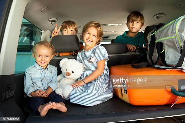 Happy kids in car boot with teddy