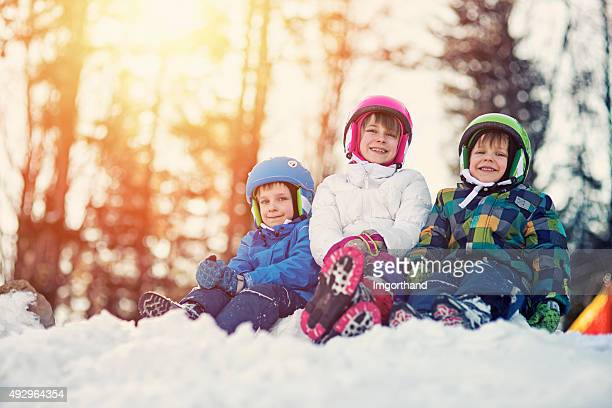 Happy kids in ski outfits enjoying winter