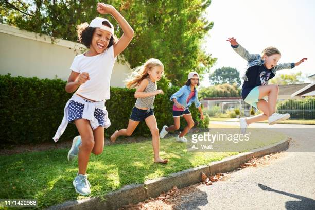 happy kids jump and play outside - playing stock pictures, royalty-free photos & images