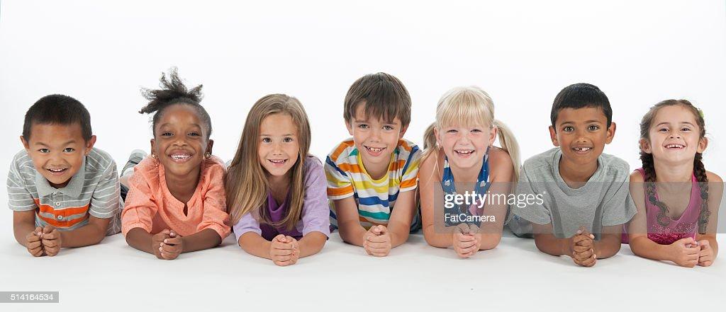 Happy Kids Lying in a Row : Stock Photo