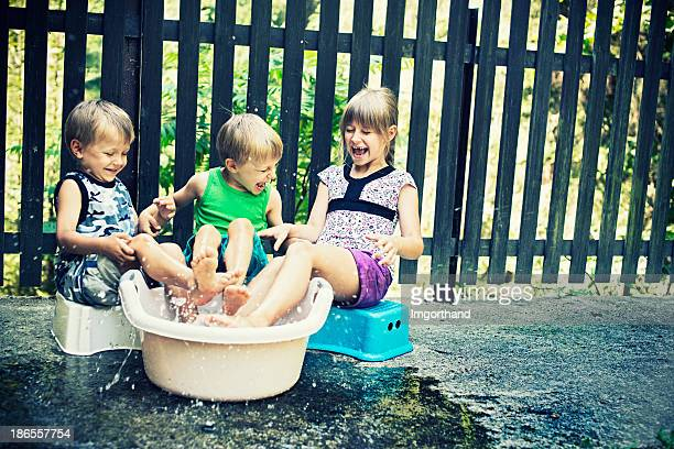 Happy kids on summer day playing with water.