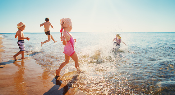 Happy kids on vacations at seaside running in the water 1044736476