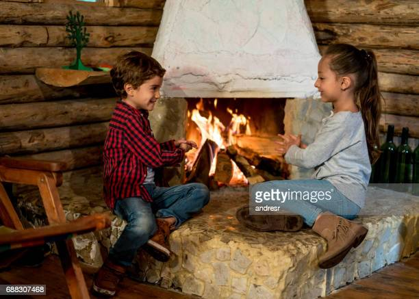 Happy kids playing at home by the fire