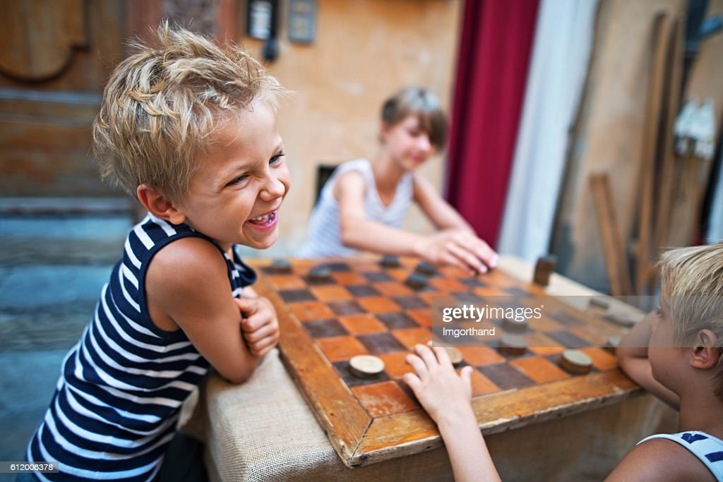 Happy kids playing checkers in the street : Stock Photo