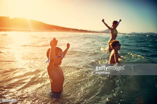 Niños felices jugando en el mar