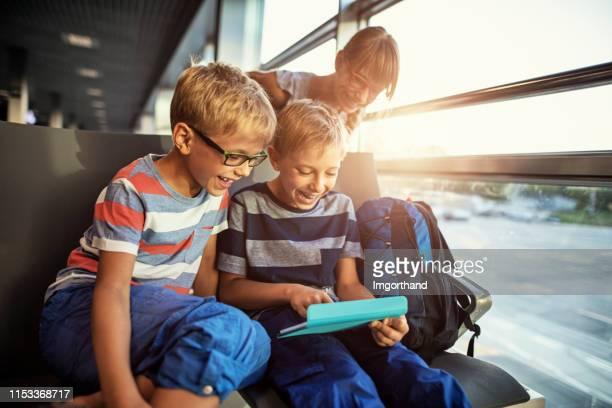 glückliche kinder spielen tablet am flughafen - kid in airport stock-fotos und bilder