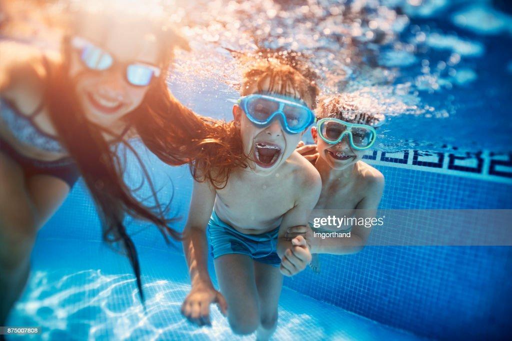 Happy kids playing underwater : Stock Photo