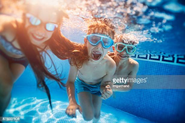 happy kids playing underwater - piscina foto e immagini stock