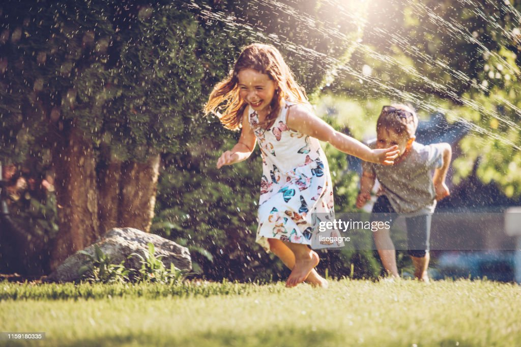 Happy kids playing with garden sprinkler : Stock Photo