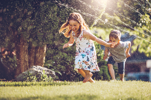 Happy kids playing with garden sprinkler 1159180335