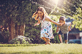 Happy kids playing with garden sprinkler