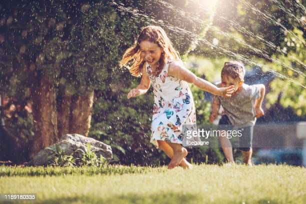 happy kids playing with garden sprinkler - summer stock pictures, royalty-free photos & images