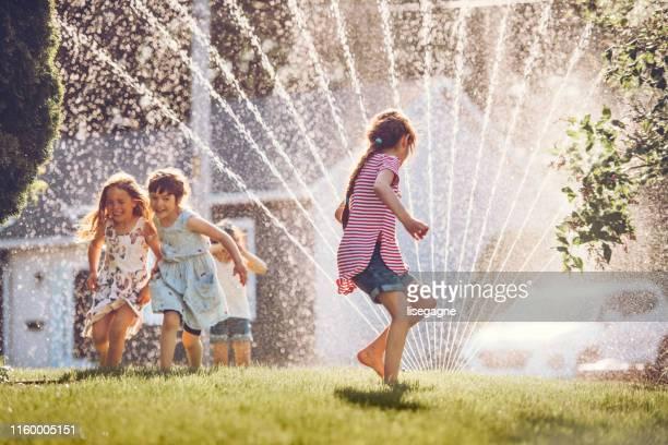 happy kids spelen met tuin sprinkler - alleen kinderen stockfoto's en -beelden