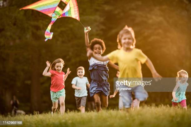 happy kids playing with kite in springtime at the park. - playing stock pictures, royalty-free photos & images