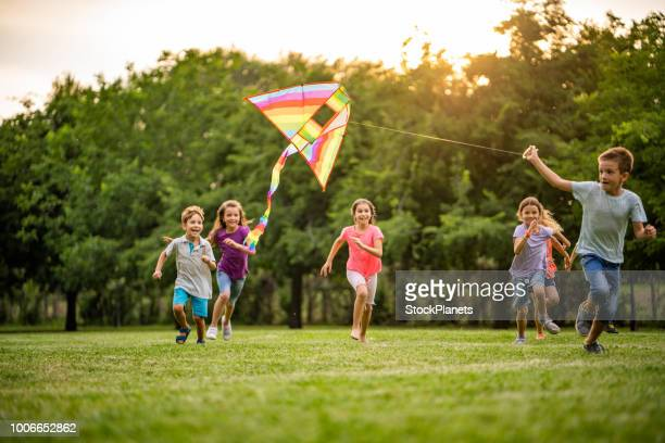 happy kids running for a flying dragon - divertirsi foto e immagini stock