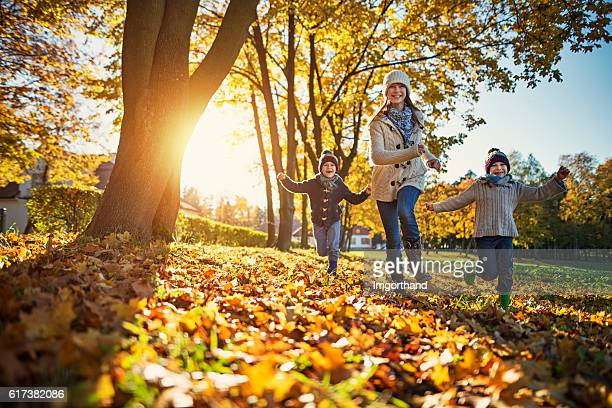 happy kids running in park on sunny autumn day. - herfst stockfoto's en -beelden