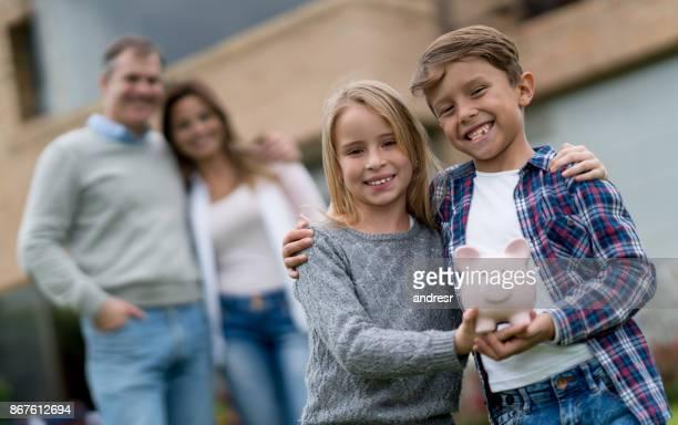 Gelukkige jonge geitjes geld besparen met hun ouders in een spaarpot