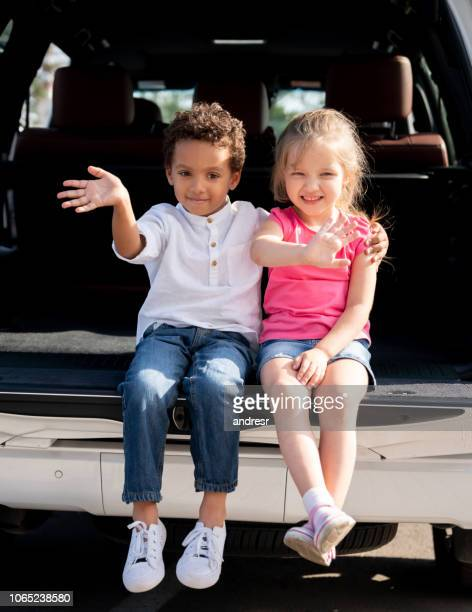 Happy kids sitting in the trunk of a car