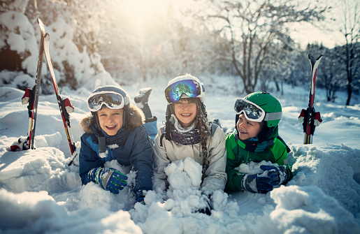 Happy kids skiing in beautiful winter forest 1064957762