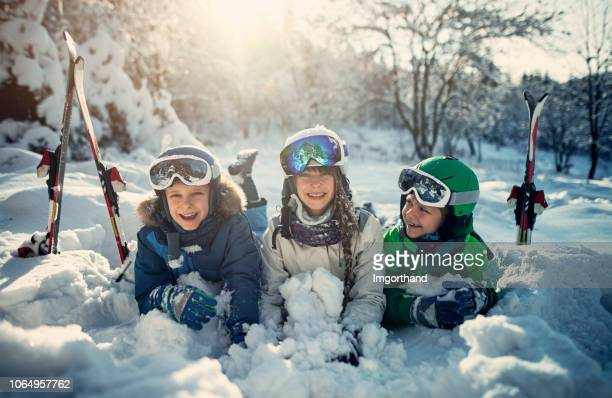 happy kids skiing in beautiful winter forest - winter sport stock pictures, royalty-free photos & images